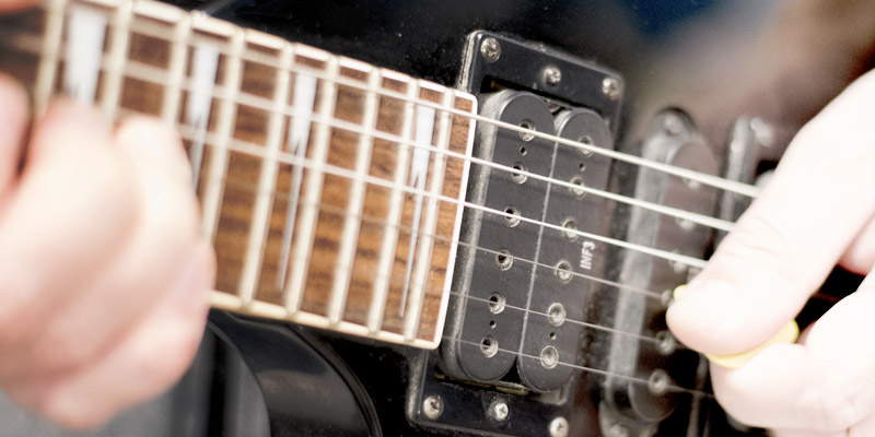 Left handed guitar being played, closeup of frets and neck pickup