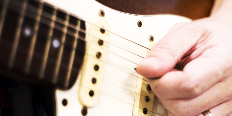 Left handed guitar being played, closeup of neck pickup