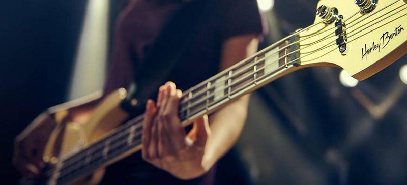 Image of someone playing a Harley Benton bass guitar.