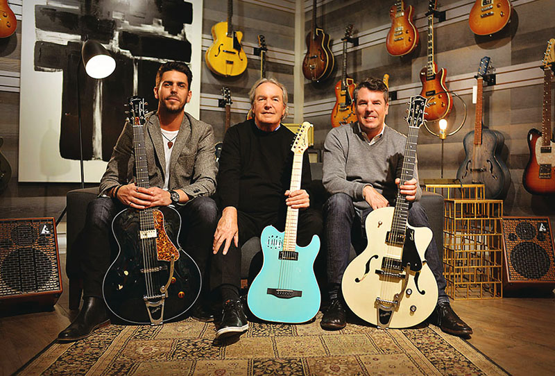 Simon, Robert, and Patrick Godin sitting in a room of guitars